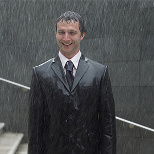 Smiling man standing in the rain