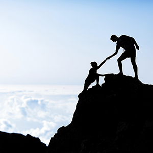 photo of person at the top of a mountain peak pulling another person up